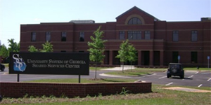 Photo of the brown brick front of the Shared Services Center building, including its sign and parking lot, located in Sandersville, Georgia.