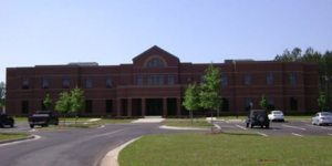 Photo of the brown brick front of the Shared Services Center building, including its parking lot, located in Sandersville, Georgia.